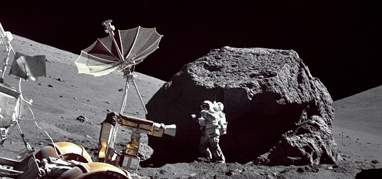 Apollo 17 astronautposes in front of large Moon rock